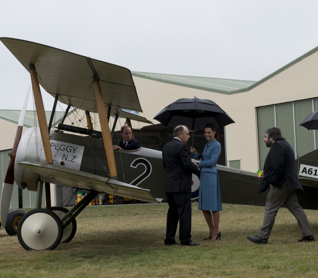 The Duke sits in a replica WWI plane while the Duchess and Peter Jackson look on